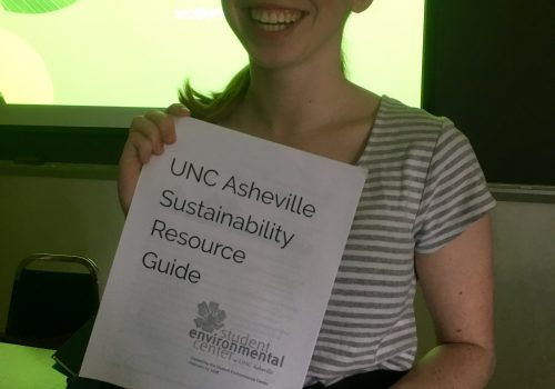 A student holding the UNC Asheville Sustainability Resource Guide